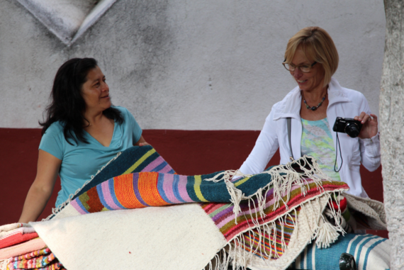 Latina women laughing and looking through rugs