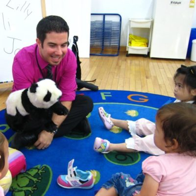 Man entertaining toddlers with panda puppet