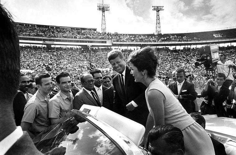 Jackie Kennedy speaking to gentlemen in stadium crowd alongside John F. Kennedy
